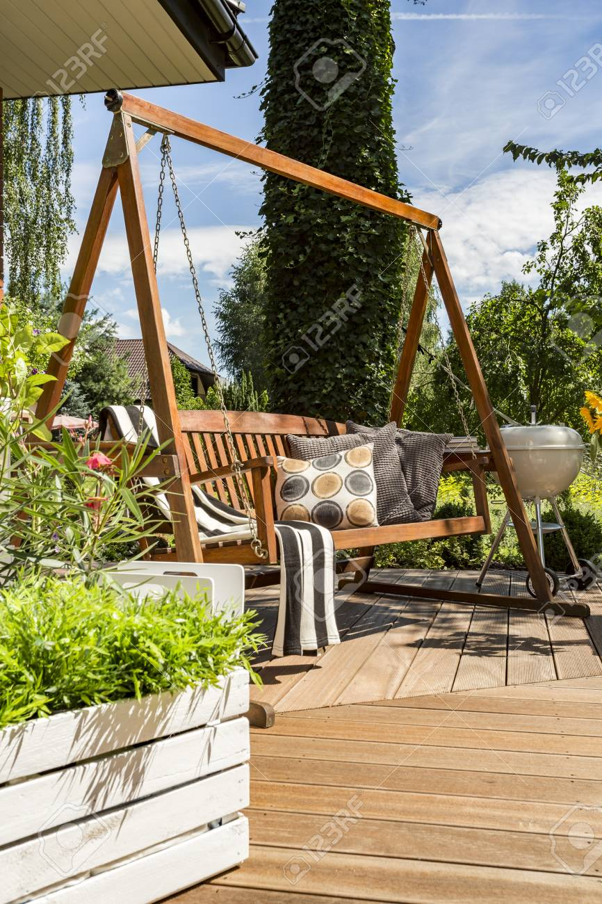 New Style Villa Patio With Wooden Garden Swing, Grill And Potted Plants  Stock Photo