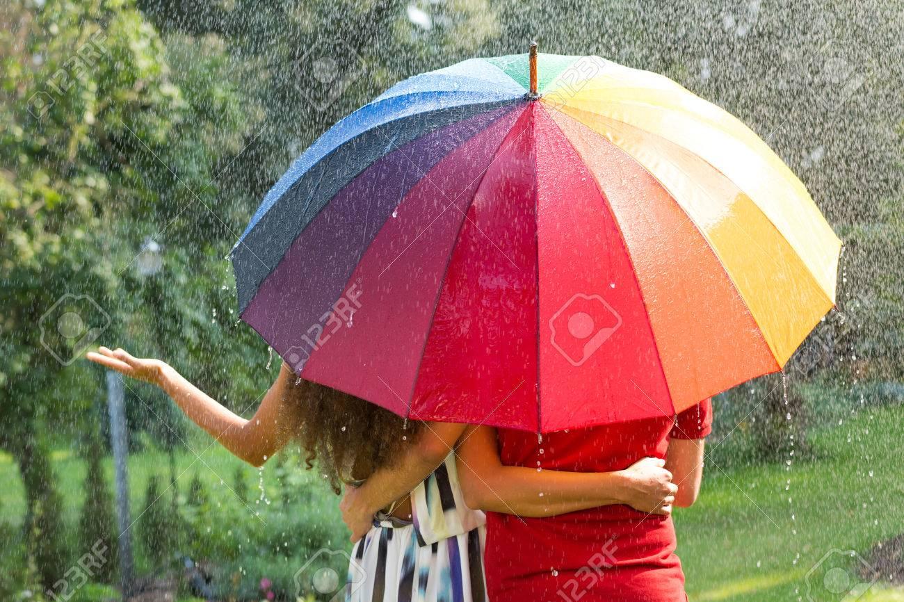 88879fb0dcef Couple under rainbow umbrella walking in the summer rain