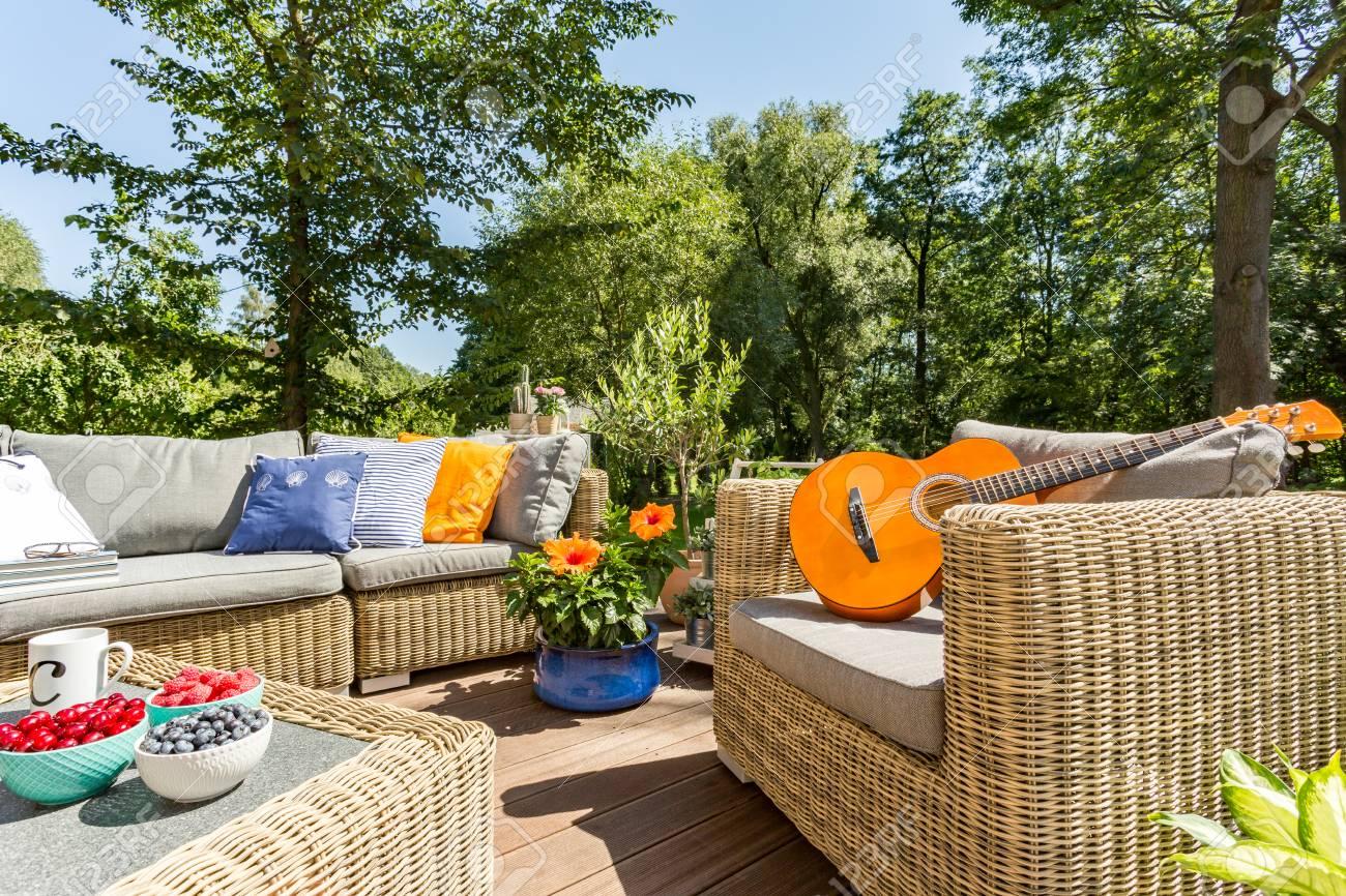 banque dimages terrasse dt avec un ensemble de meuble en rotin une guitare allonge sur un fauteuil en rotin - Meuble Terrasse