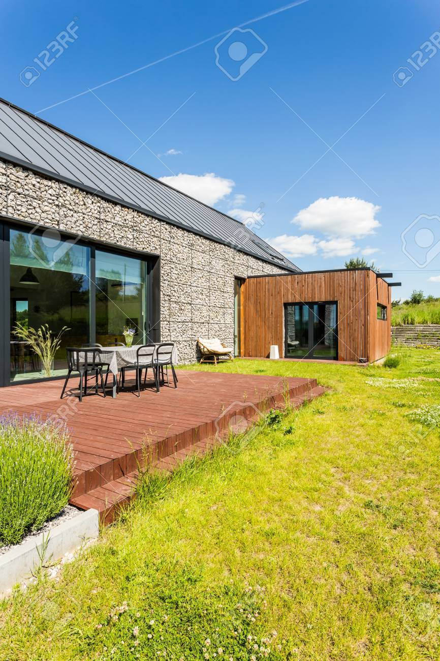 Eco Friendly Backyard House Design With Simple Wooden Terrace Stock