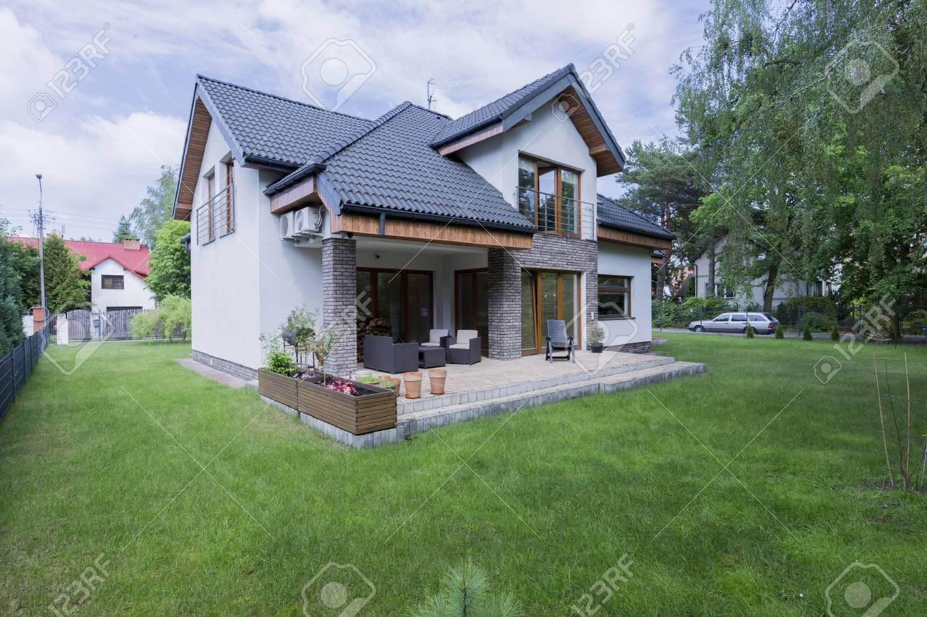 Détaché extérieur de la maison moderne avec terrasse entouré de pelouse  verte coupée