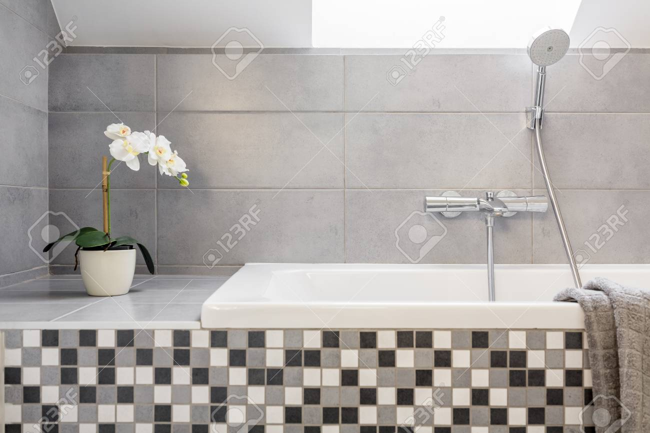 Salle de bains gris avec des carreaux de mosaïque et baignoire