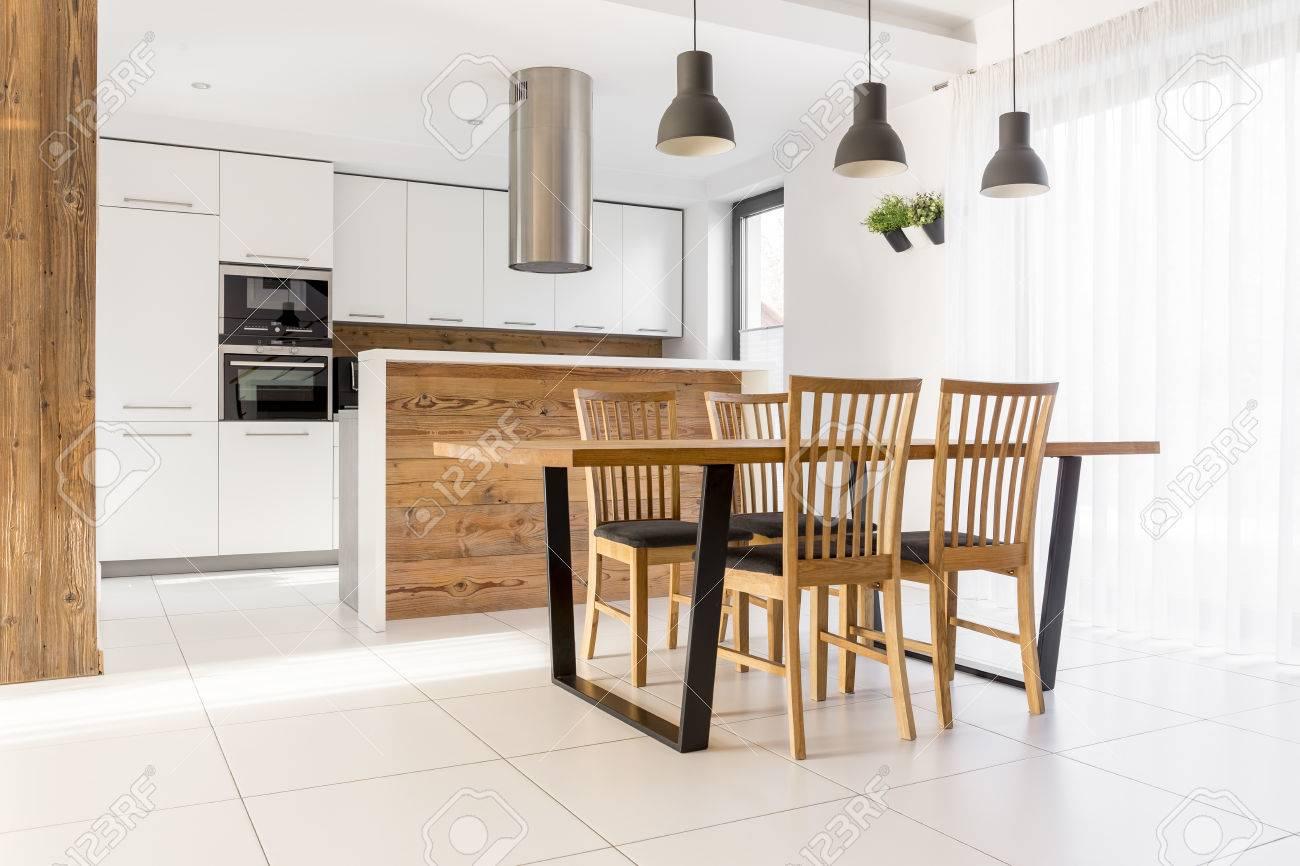 Nouvelle cuisine blanche avec table en bois, chaises et îlot