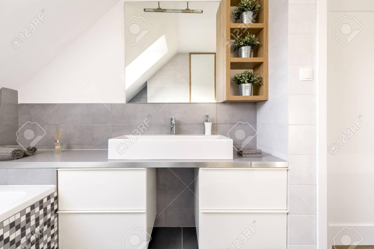 Cuarto de baño gris con armarios blancos y espejo