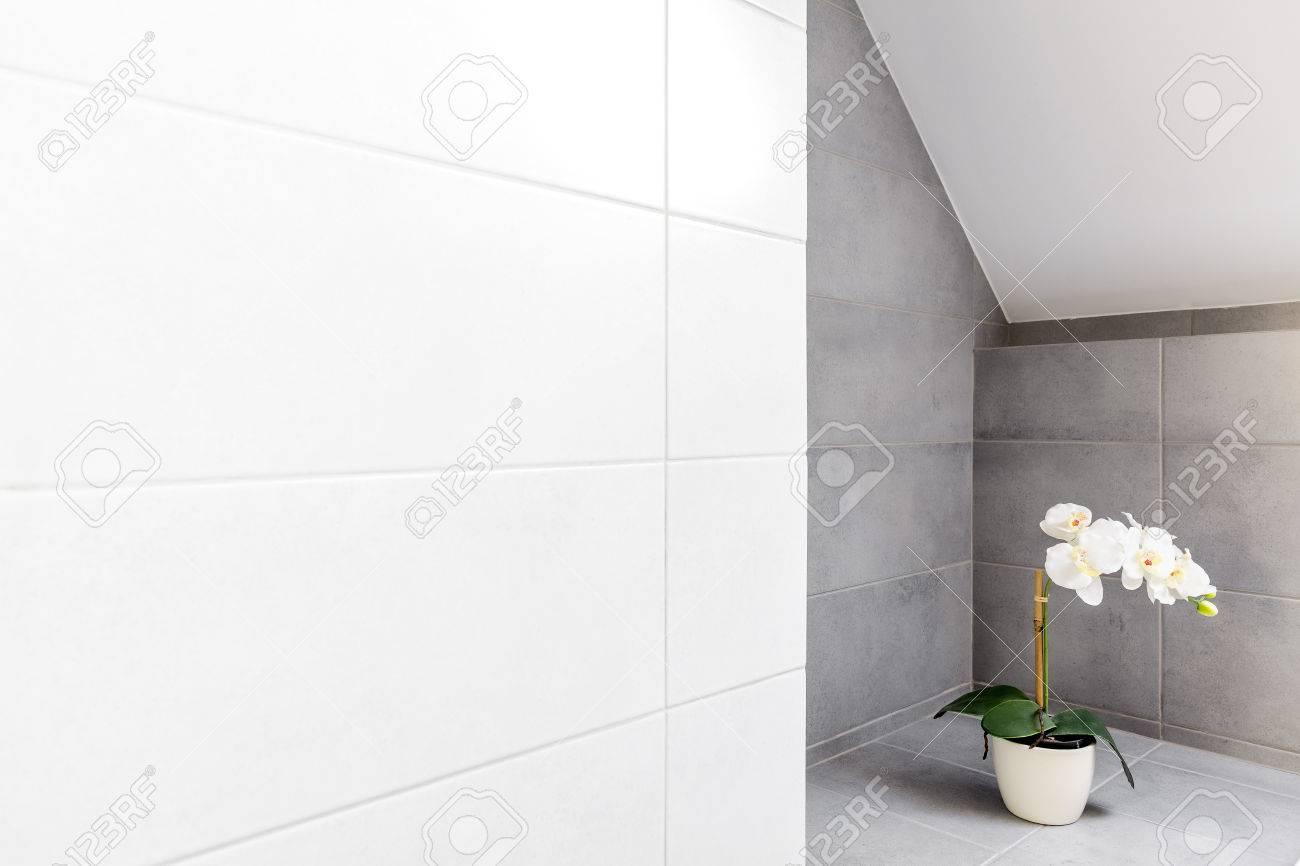 Salle de bain avec carrelage mural gris et blanc et orchidée décorative