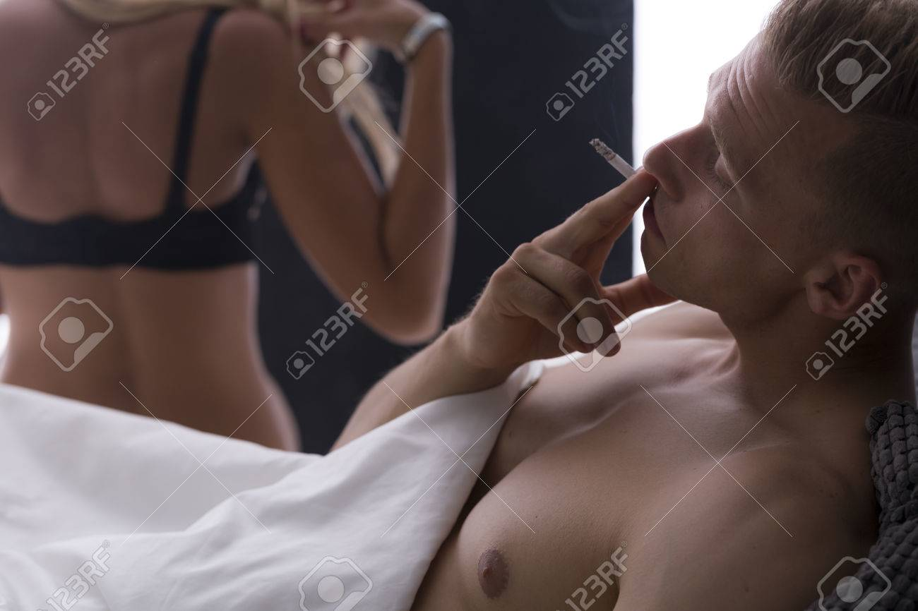 young handsome man smoking cigarette in bed after sex stock photo
