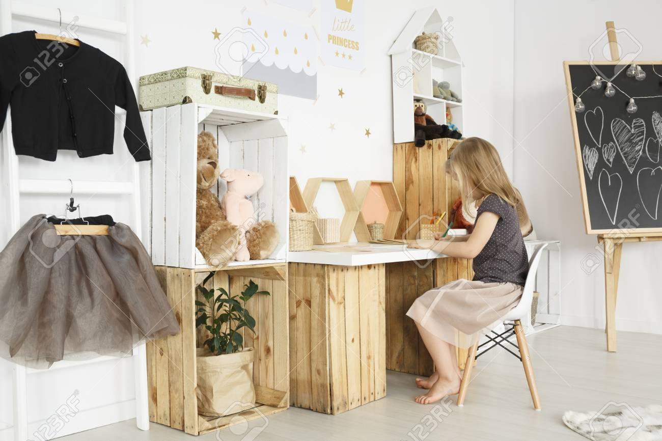 Petite fille assise à un bureau dans une chambre moderne et