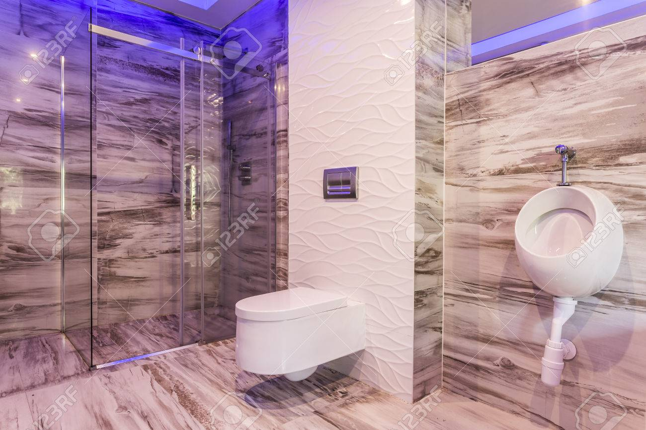 Marble bathroom with urinal toilet and glass shower enclosure stock