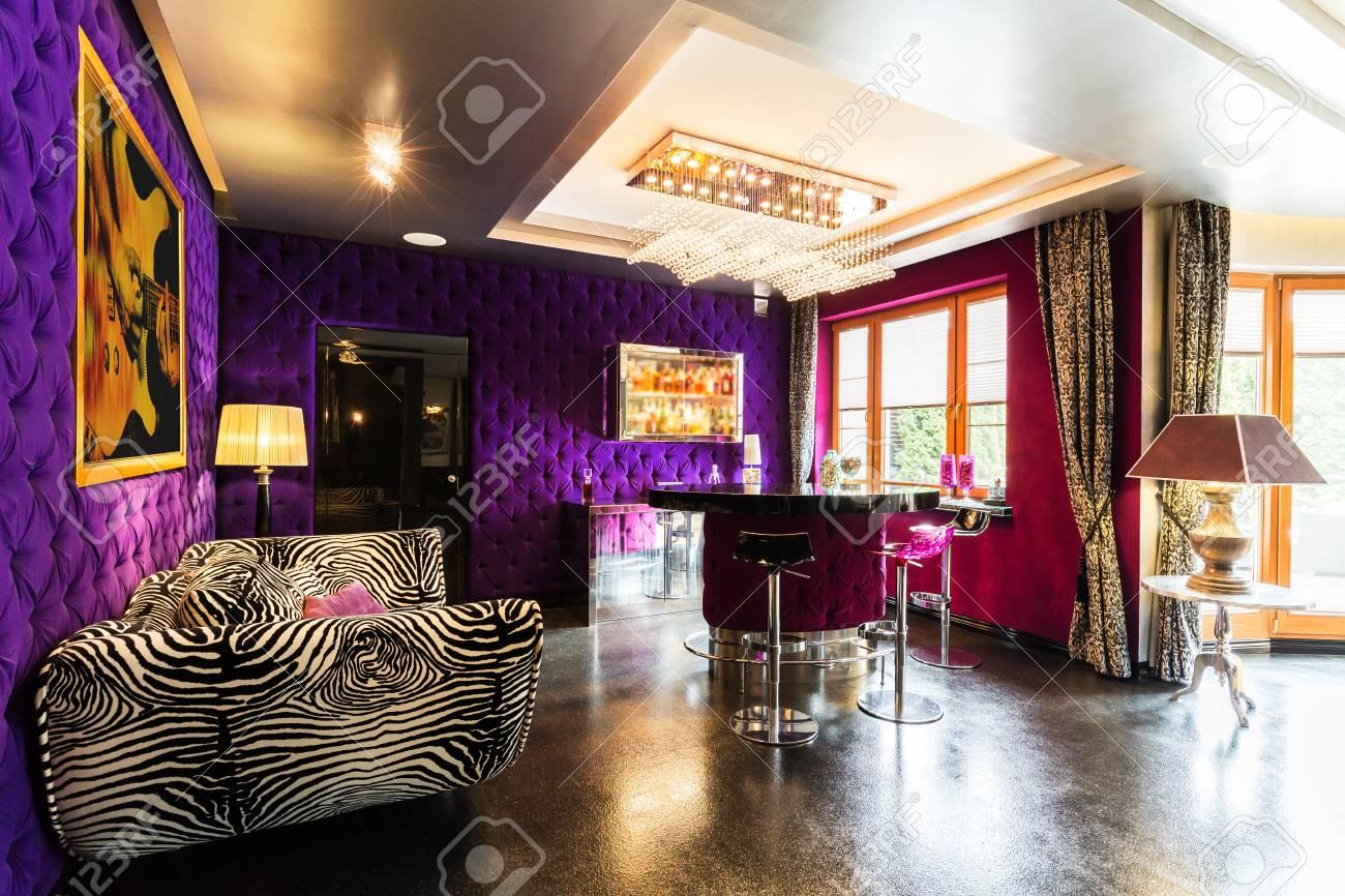 Modernes Wohnzimmer Mit Violett Gepolsterten Wänden, Glitzerboden,  Muster Zebra Sofa, Stehtisch