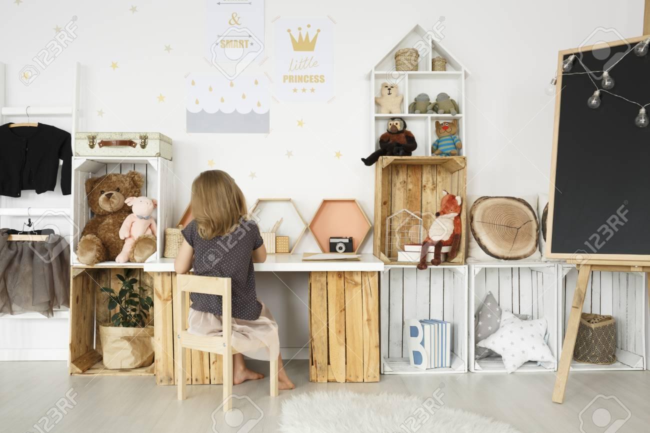 Petite fille assise à son bureau dans une salle scandi avec des