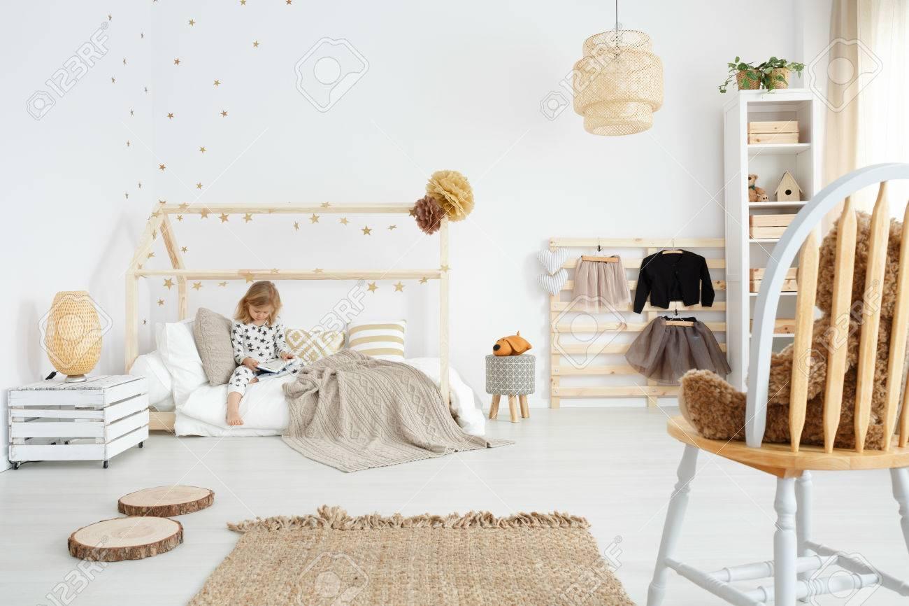Kleines Mädchen Sitzt Auf Ihrem Bett Im Weißen Skandinavischen ...