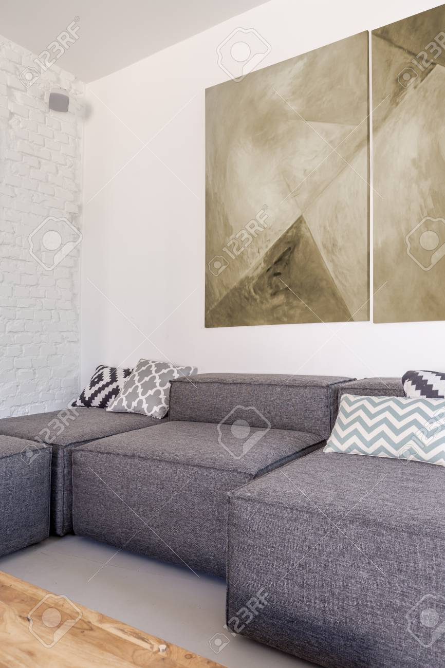 Grey fabric corner sofa in trendy simple living room