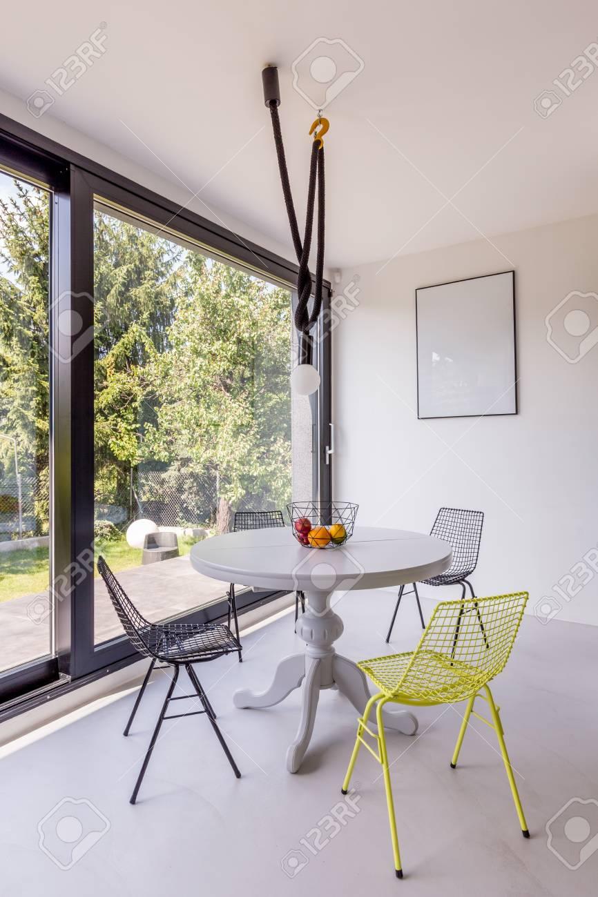 Mesa redonda y sillas de metal en un pequeño comedor elegante con ventana  panorámica