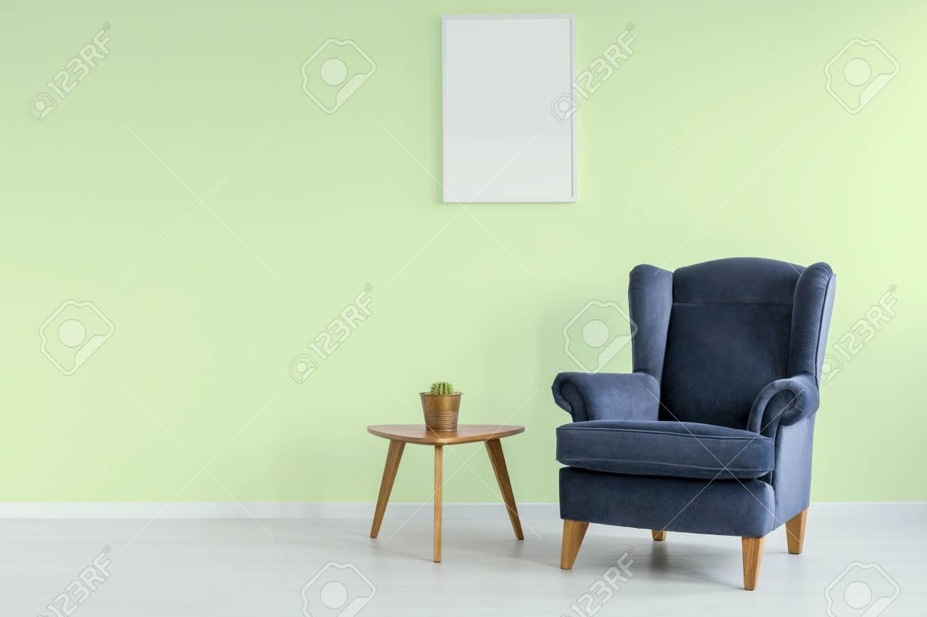 Chambre verte simple avec fauteuil bleu et oreiller coloré