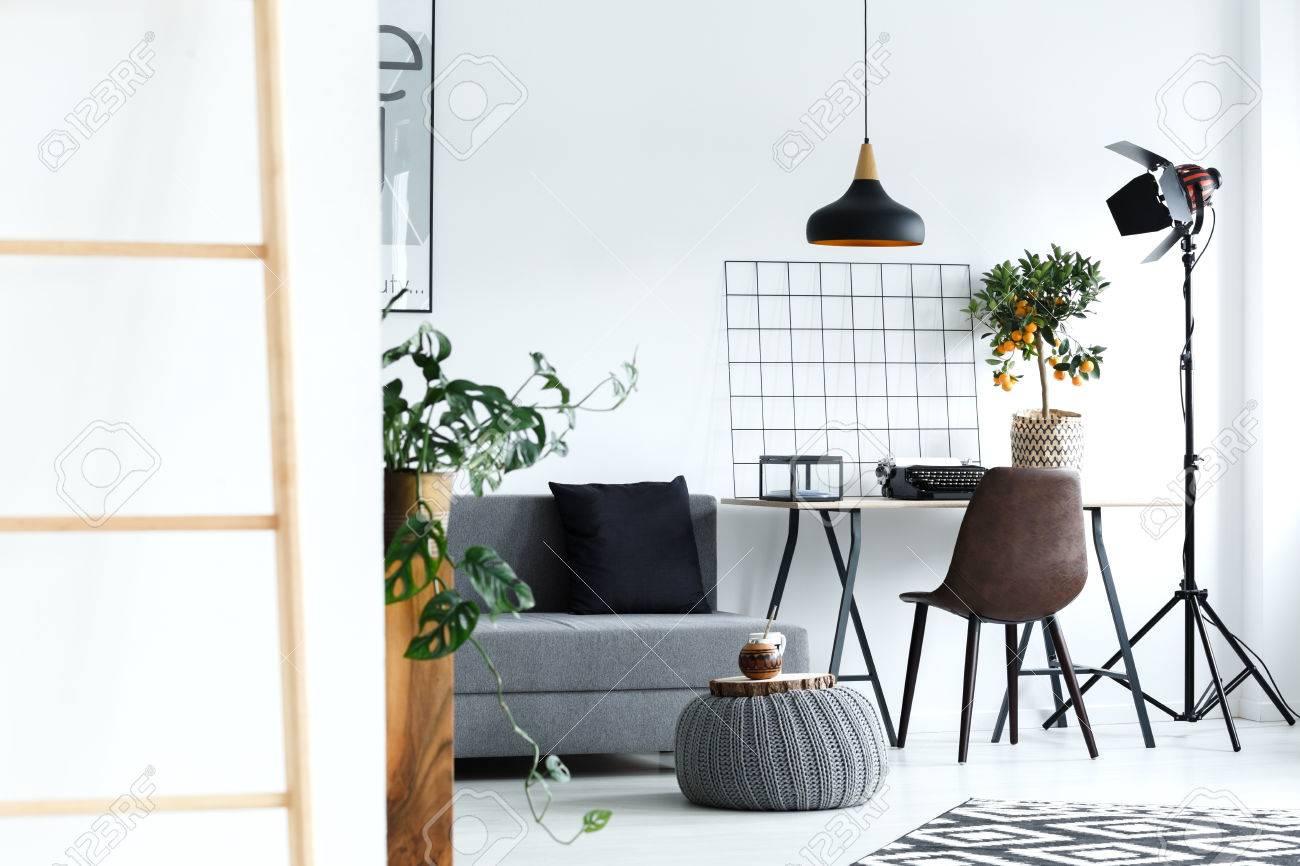 Salon blanc minimaliste avec canapé gris lampe bureau échelle