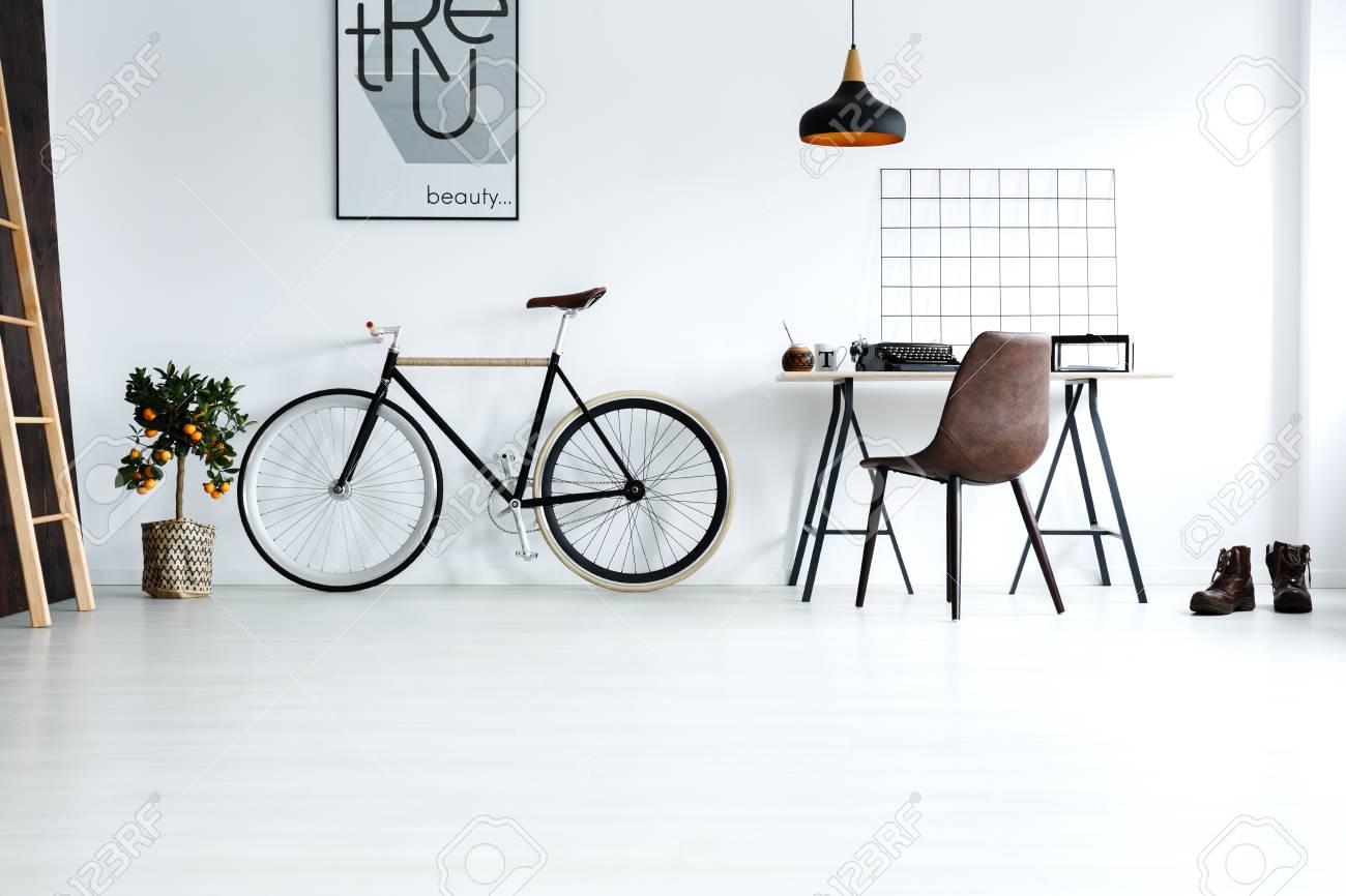 Chambre simple et blanche avec vélo bureau chaise lampe