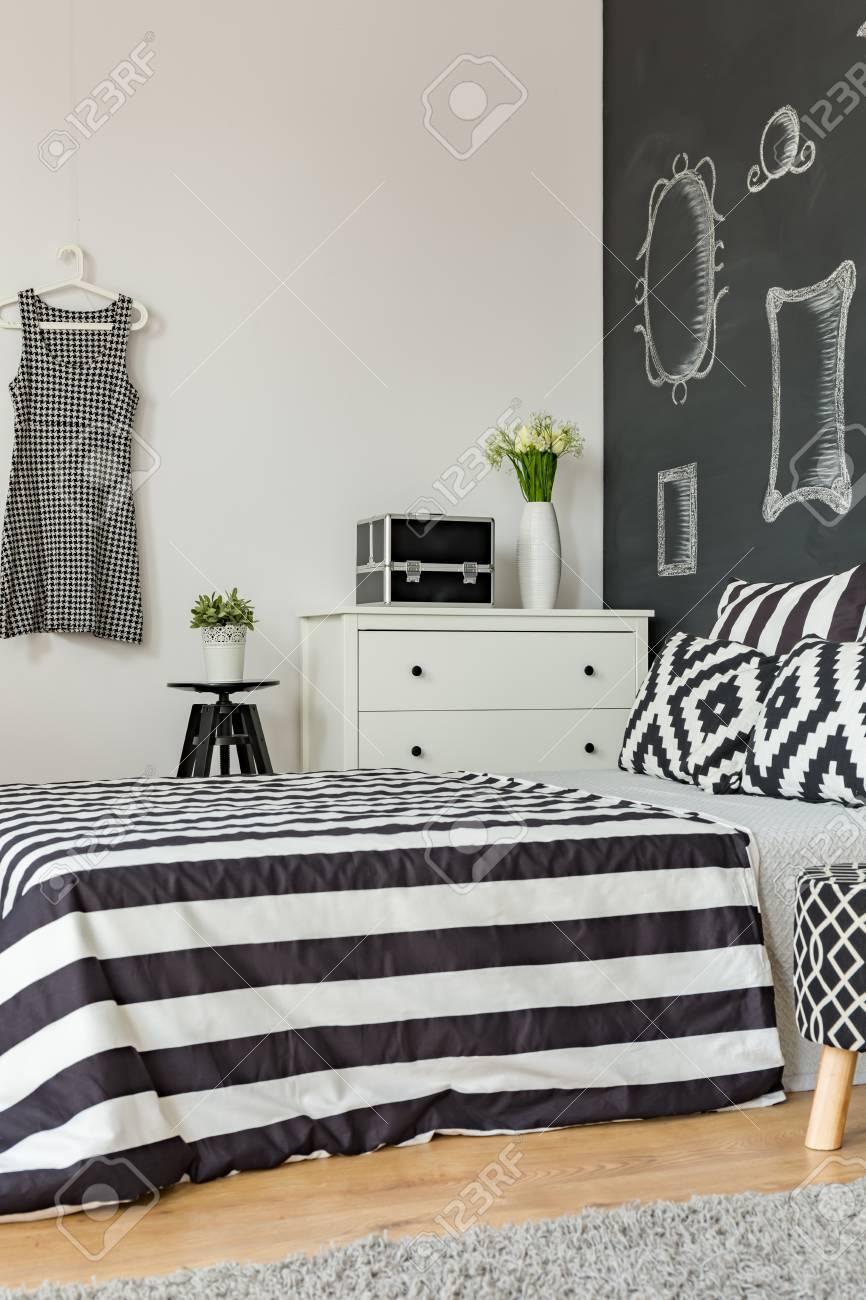 Chambre féminine en noir et blanc avec lit et mur de tableau noir à la mode