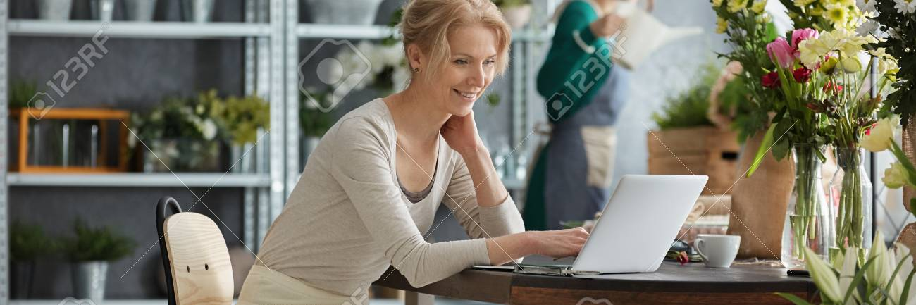 Young blonde woman with laptop and flowers on the desk - 77982172