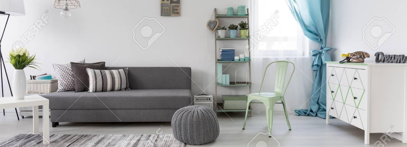 Nouveau salon de style scandinave avec canapé gris et commode blanche,  panorama