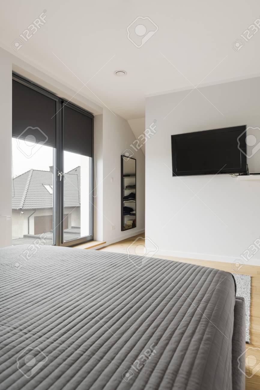 Modernes Gemütliches Schlafzimmer Mit Grauem Doppelbett Und TV An Der Wand  Standard Bild   78504389