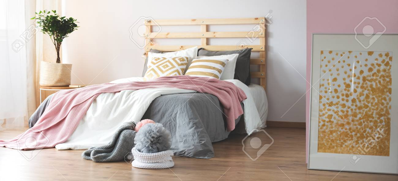 Cozy modern bedroom with wooden floor and grey and pink decor
