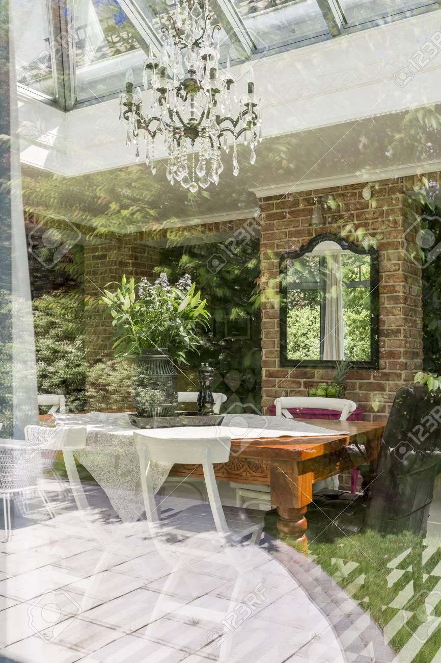 Vista de un comedor con mesa, sillas, espejo y la araña hecha por fuera