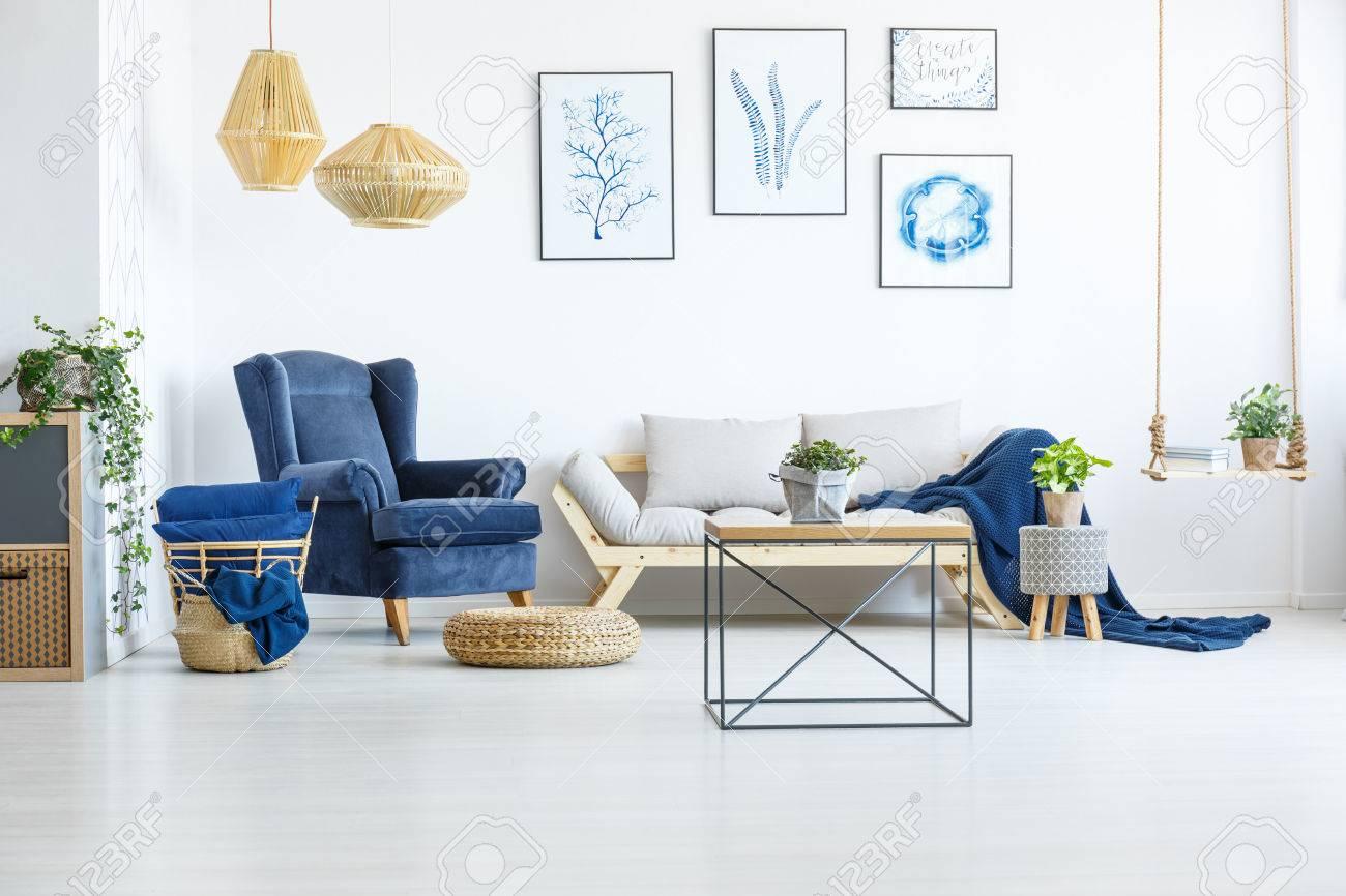 Salon blanc avec fauteuil bleu marine, canapé et affiches
