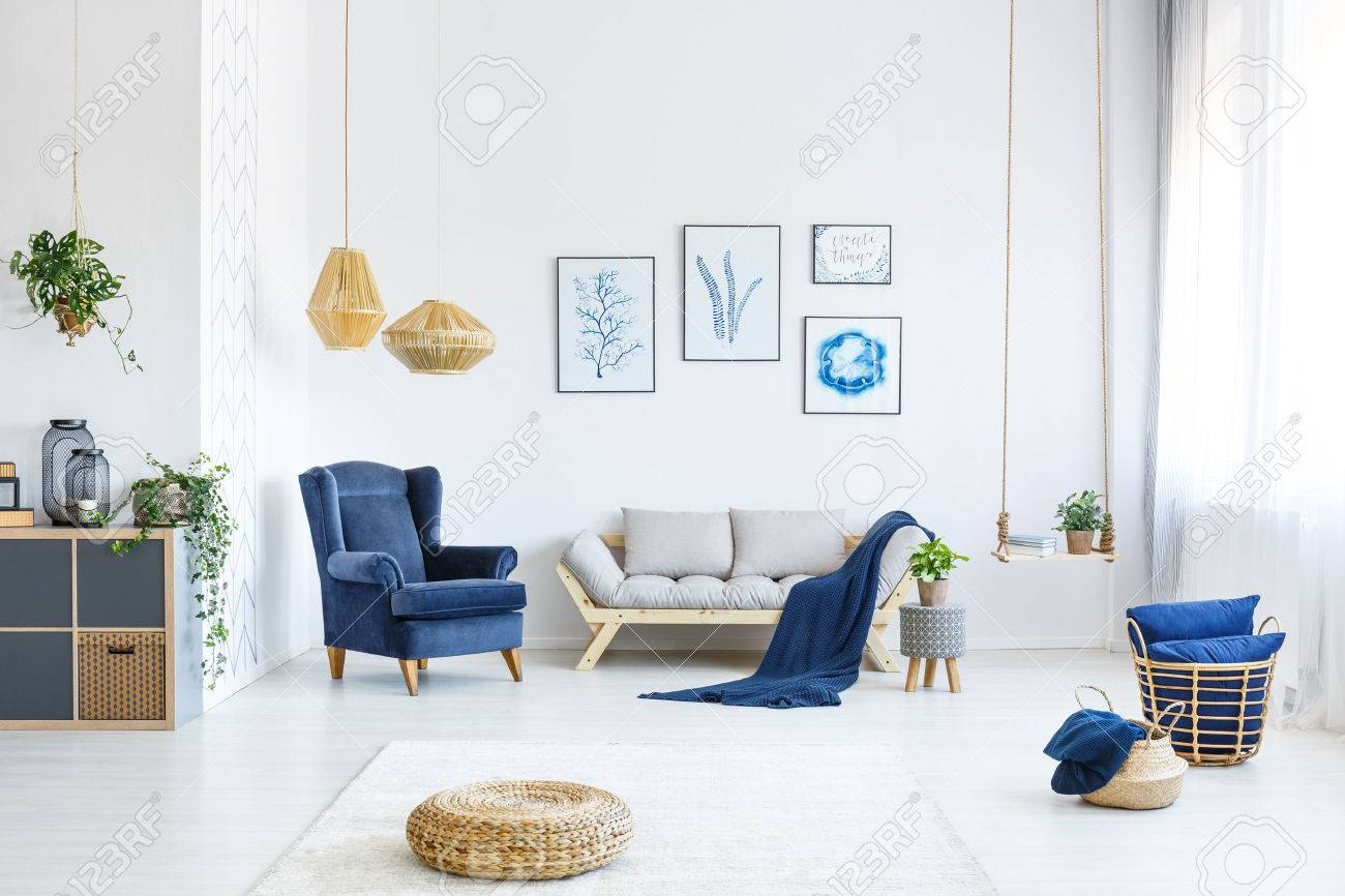 White Living Room With Wood Sofa, Blue Armchair, Lamps, Posters ...