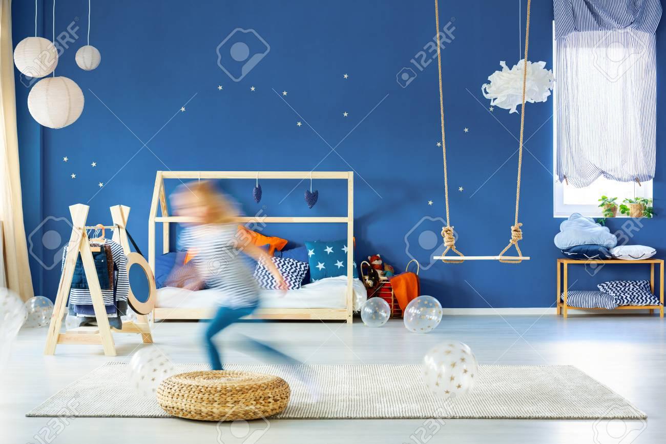 Chambre d\'enfant avec mur bleu marine, lit en bois et balançoire