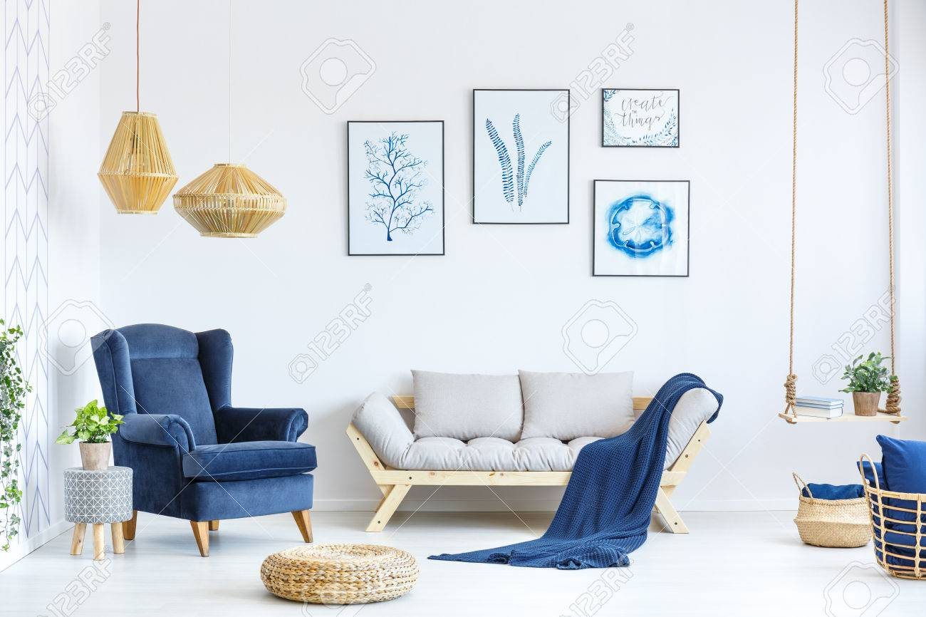 White and blue living room with sofa, armchair, lamp, posters Stock Photo - 78950093