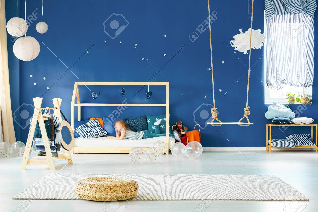 Modern girl room with swing, bed and navy blue wall