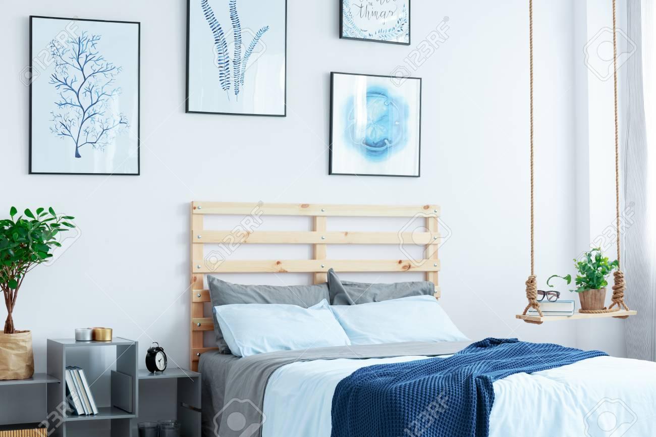 Chambre Blanche Et Bois chambre blanche avec lit en bois, étagère pivotante, affiches murales,  plantes