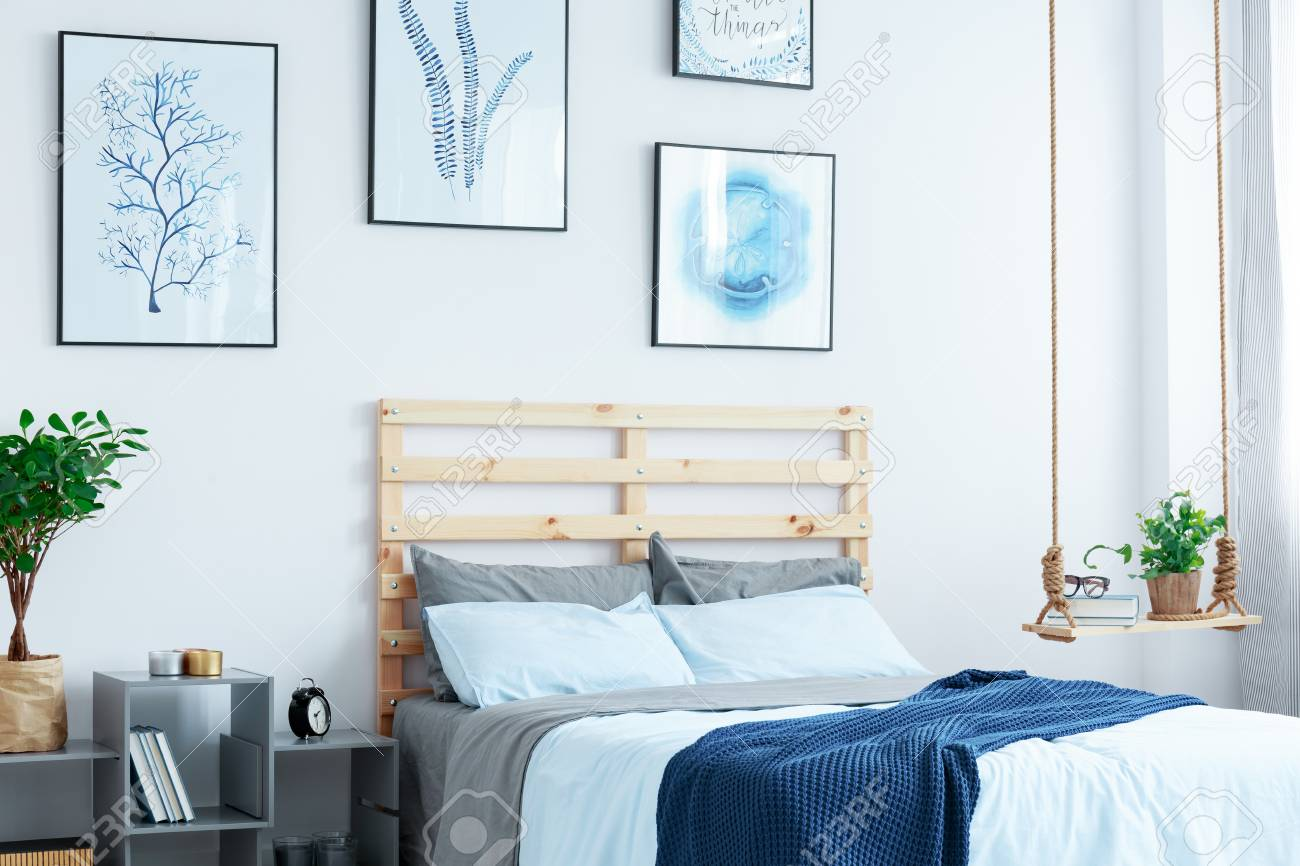 White bedroom with wood bed, swing shelf, wall posters, plants