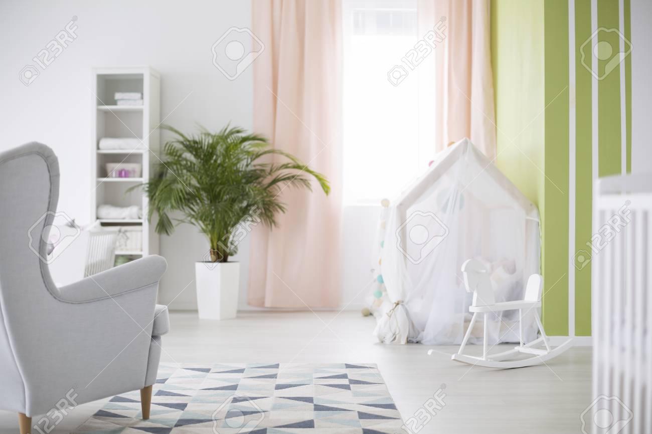 e29a3b40f Foto de archivo - Tienda de juegos blanca y caballito de balancín en la  acogedora habitación de bebé