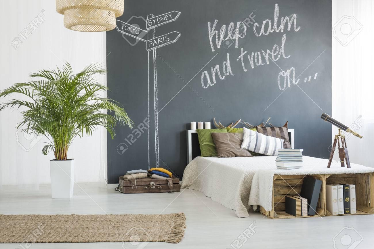 Charmante chambre blanche de voyageur avec tableau noir derrière le lit