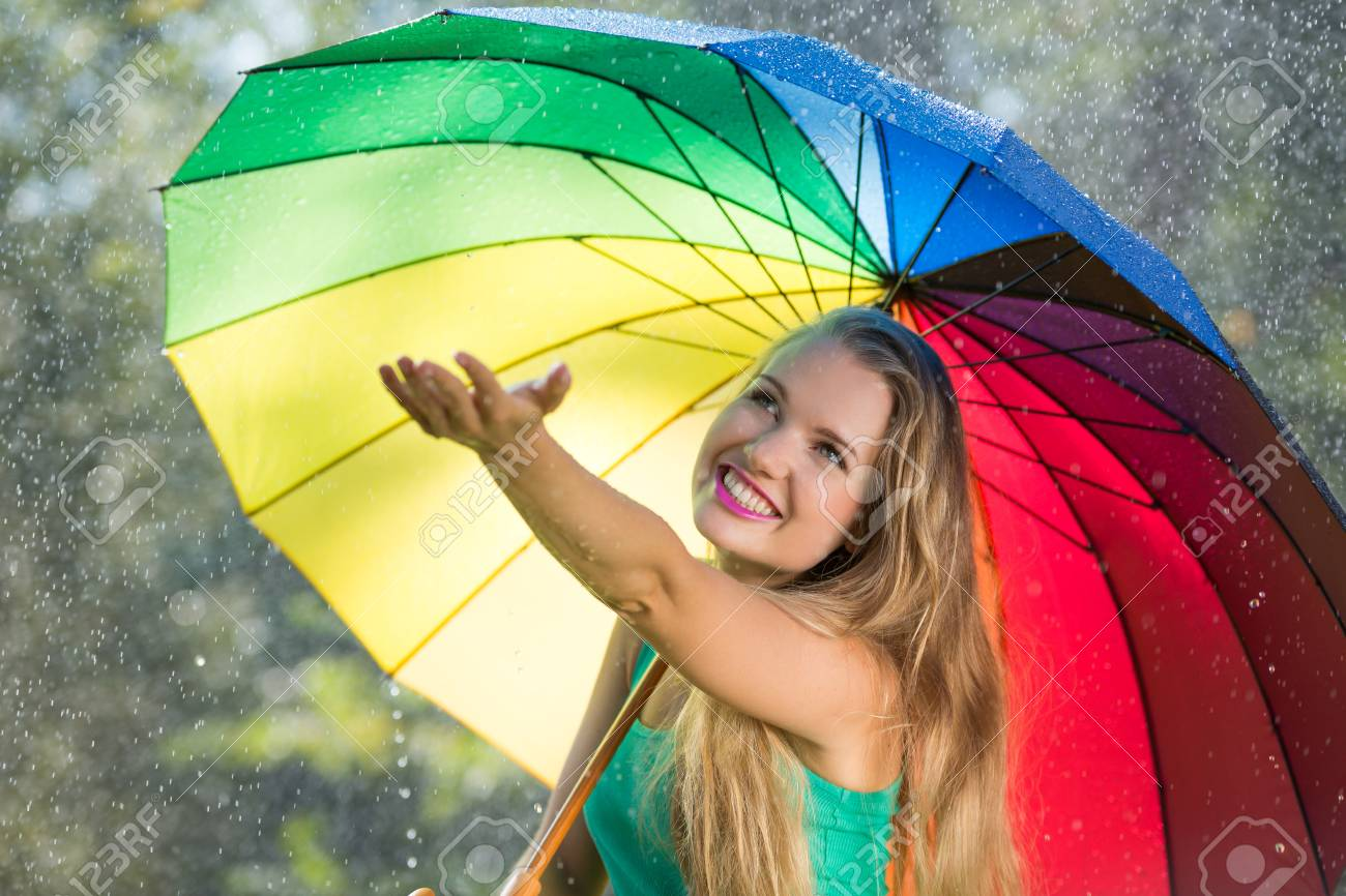 4e2e5d3f8f2 Blonde girl with colorful umbrella checking for rain Stock Photo - 79393114