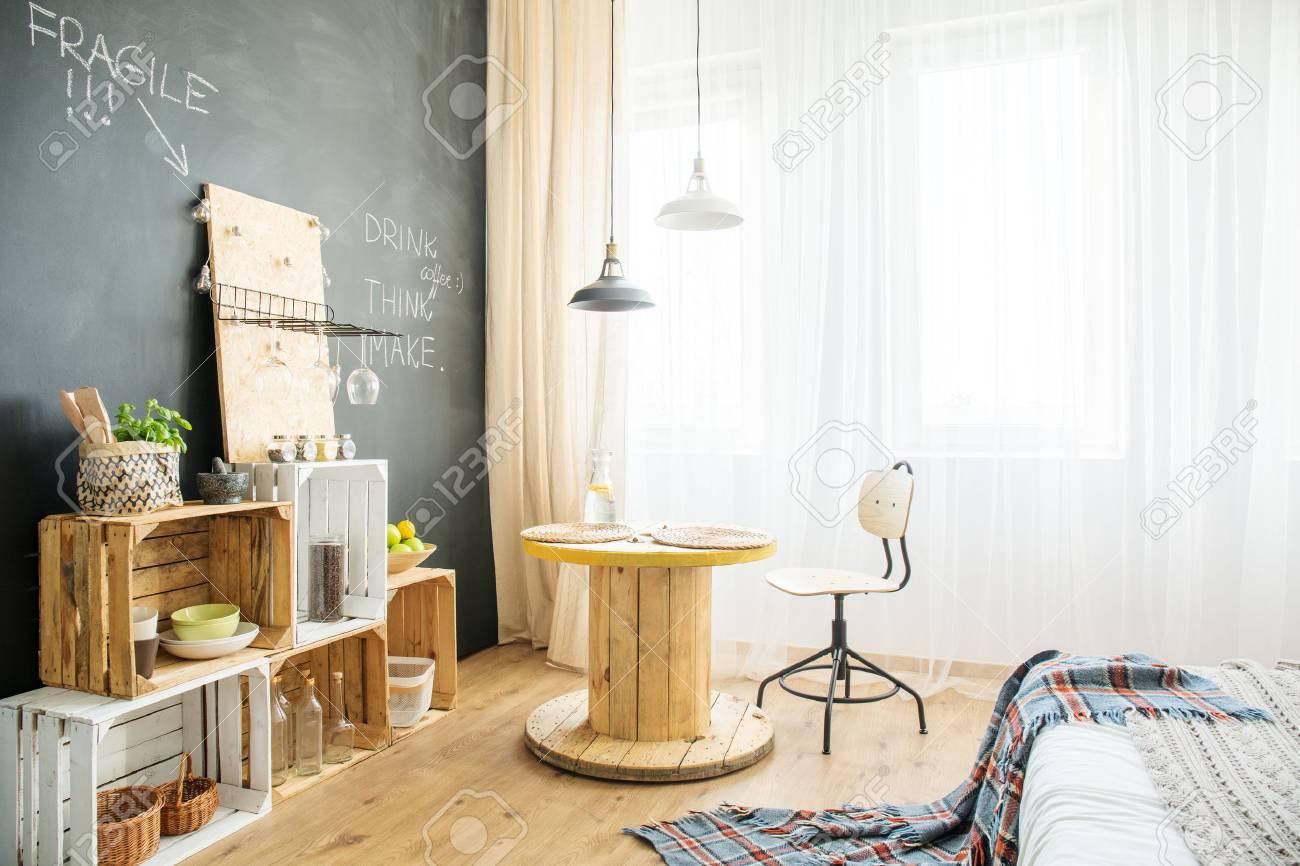 modernes Öko-studio-apartment mit kisten, tisch und bett lizenzfreie