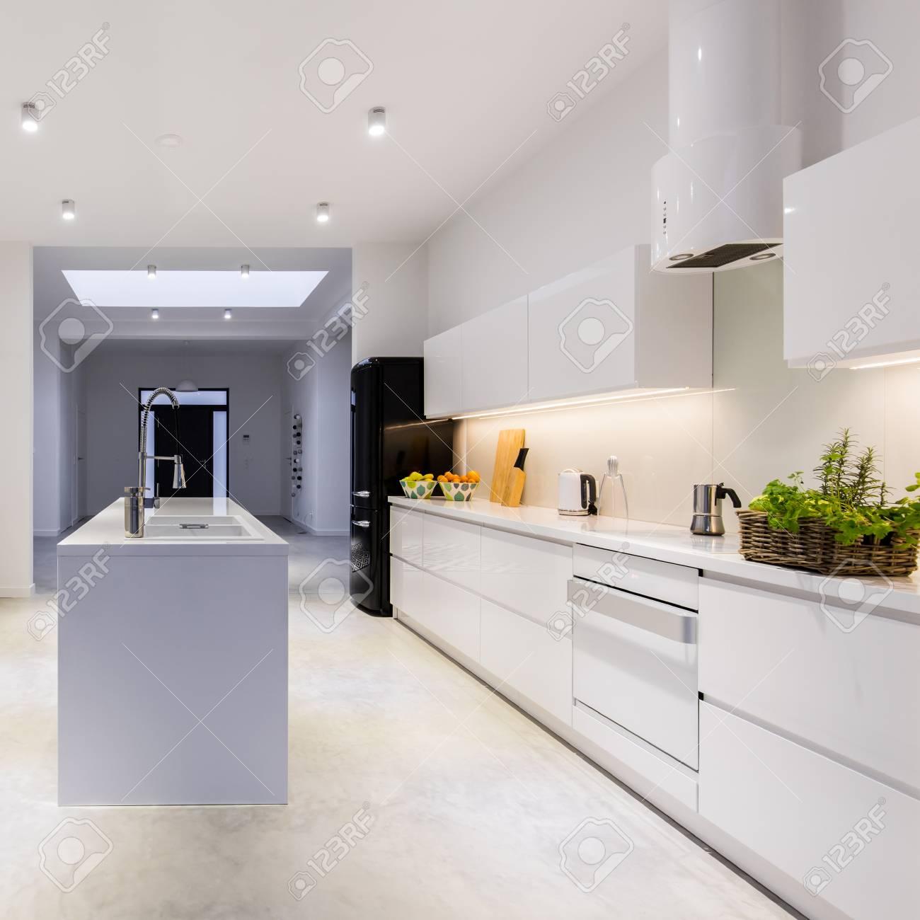 Moderne, Helle Küche Mit Kücheninsel In Der Mitte Und Weißen Einfachen  Schränken Standard Bild