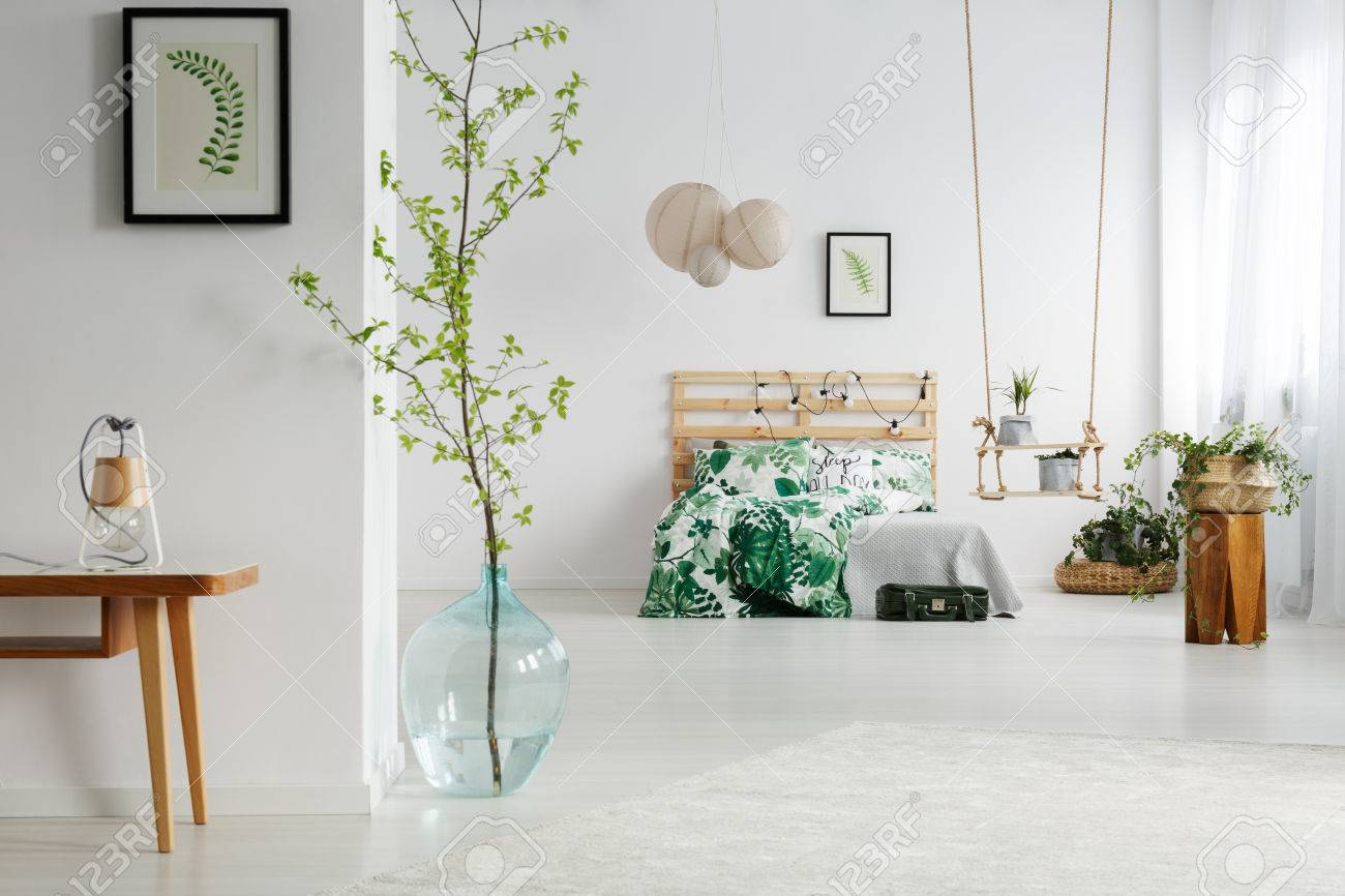 Chambre blanche avec des plantes vertes, lit en bois et balançoire