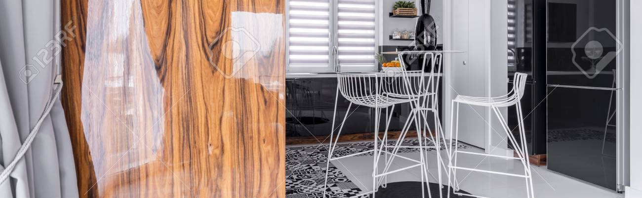 Disegno cucina interna con mobili in bianco e nero e sedie moderne