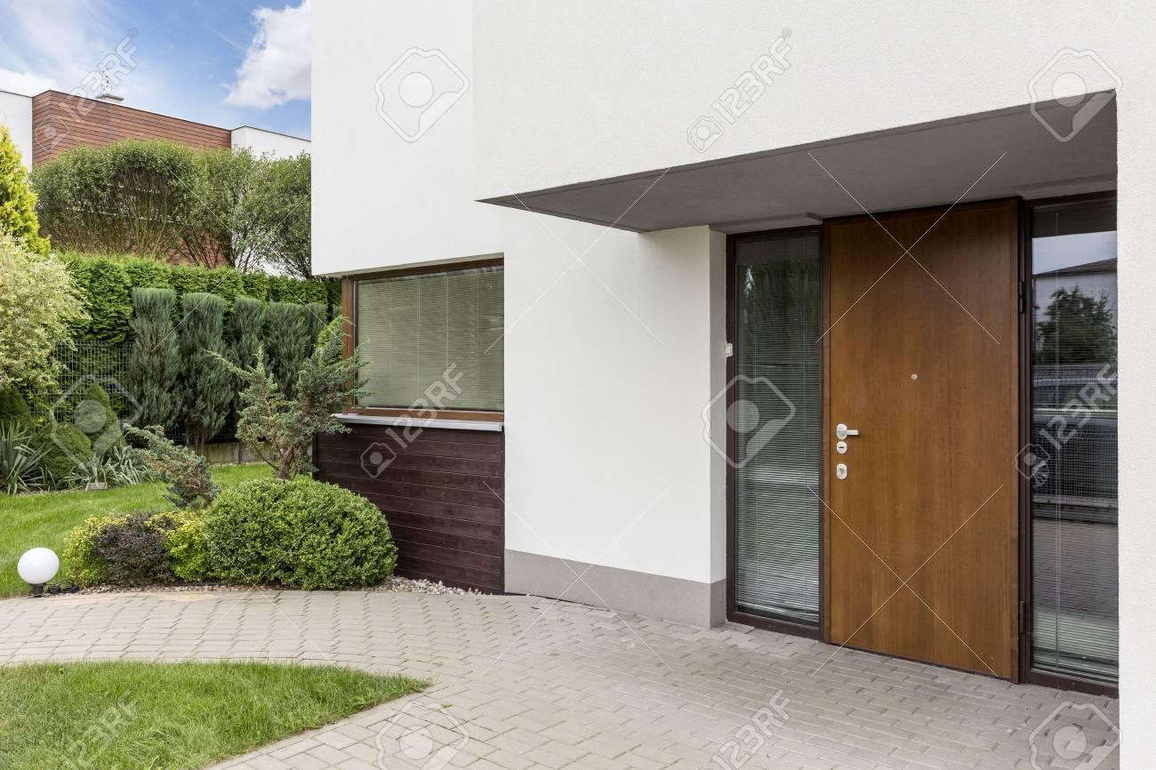 Maison Blanche Et Grise porte d'entrée en bois à la maison blanche moderne avec allée pavée et  jardin à l'arrière