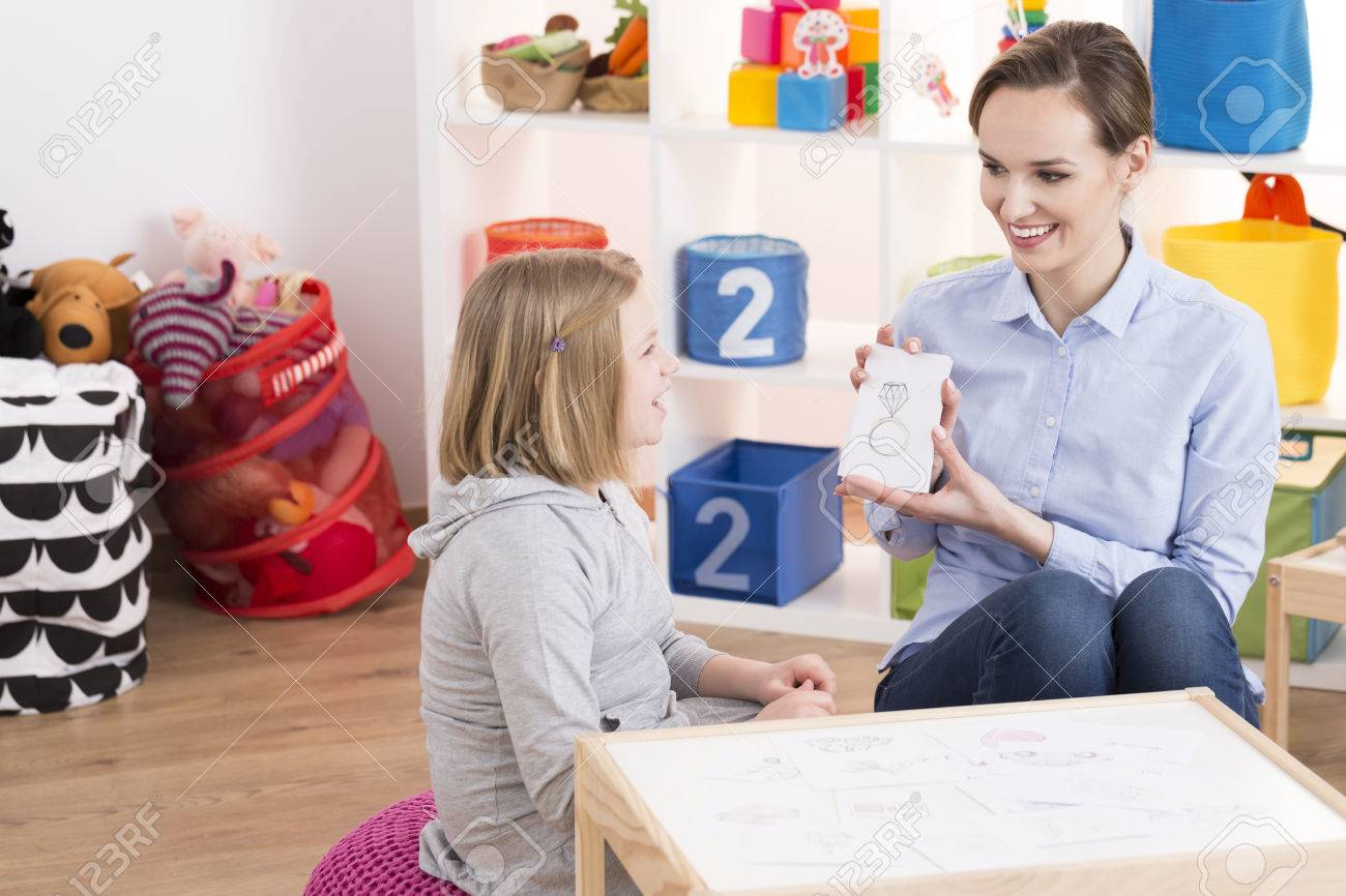 Child counselor showing drawings to little smart girl with ADHD Banque d'images - 80159731