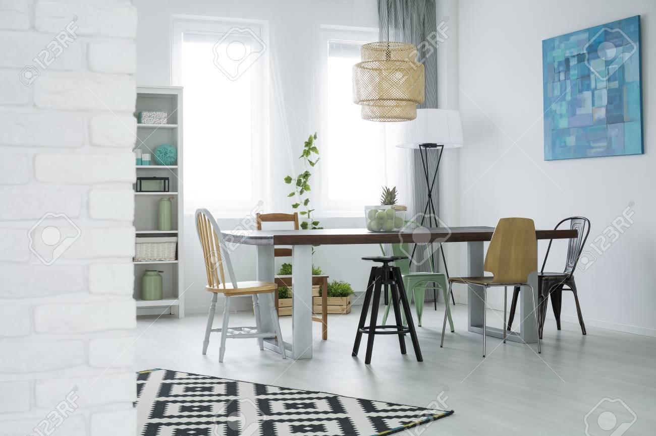 Comedor con pared de ladrillo, mesa, sillas, biblioteca, lámpara de ratán