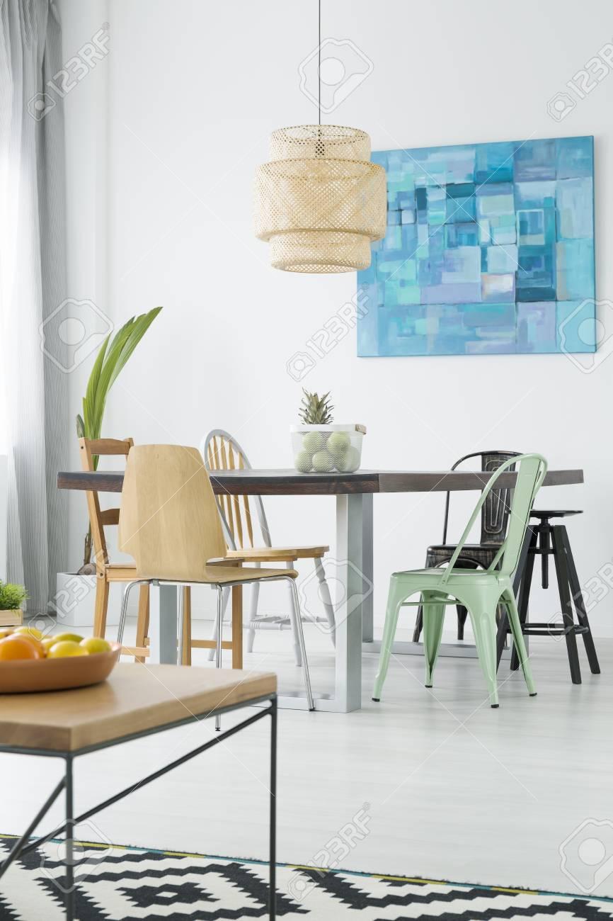 Piso blanco con mesa de comedor, sillas, lámpara y alfombra de patrones