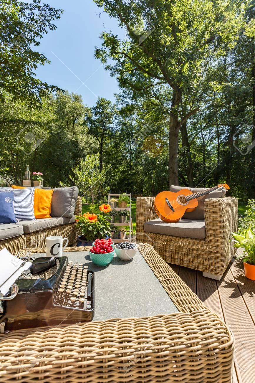 Acogedor Jardín Con Muebles De Mimbre En Un Día Soleado De Verano ...