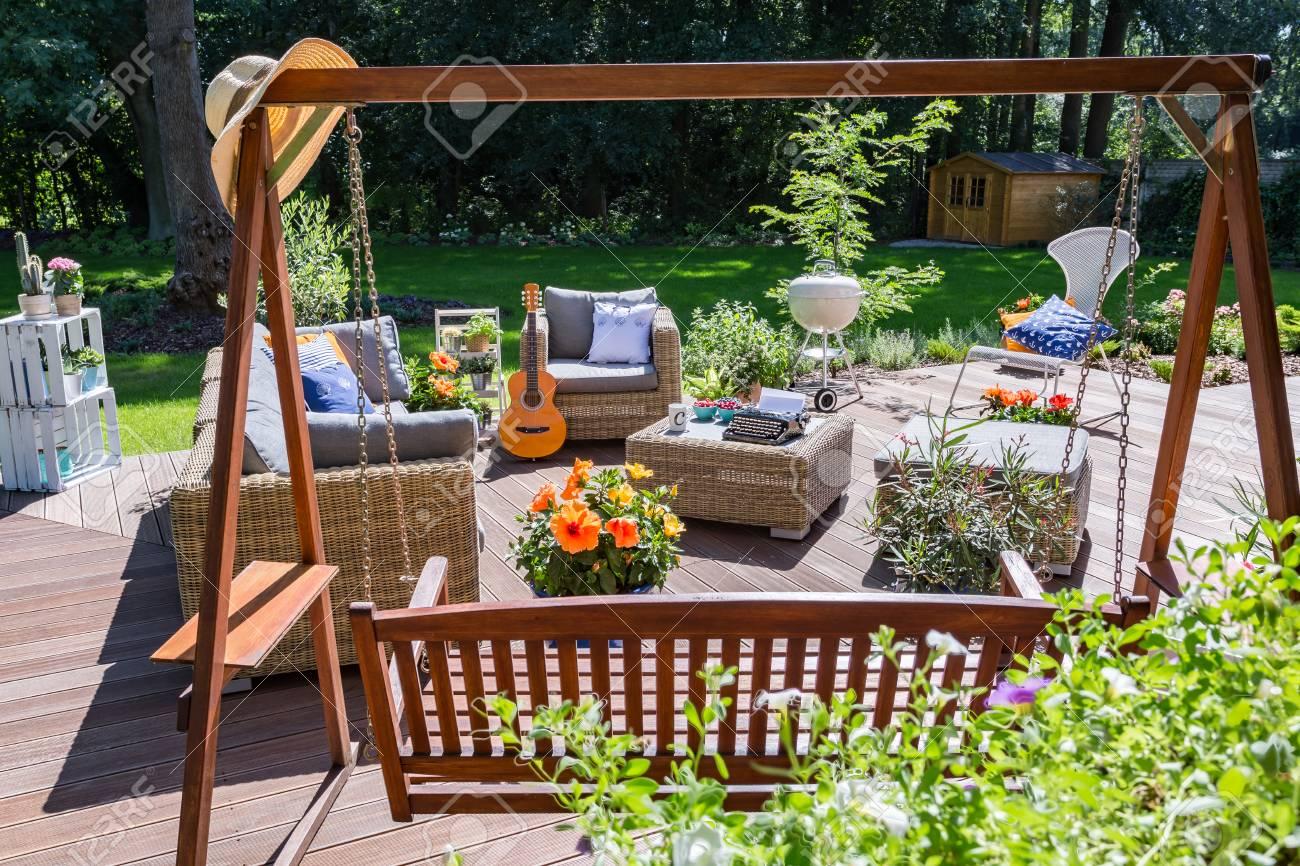 Amplia Terraza Con Un Gran Jardín Swing Y Muebles De Mimbre