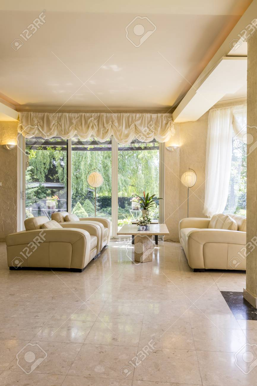 Beige living room in luxurious style with small table and comfortable..