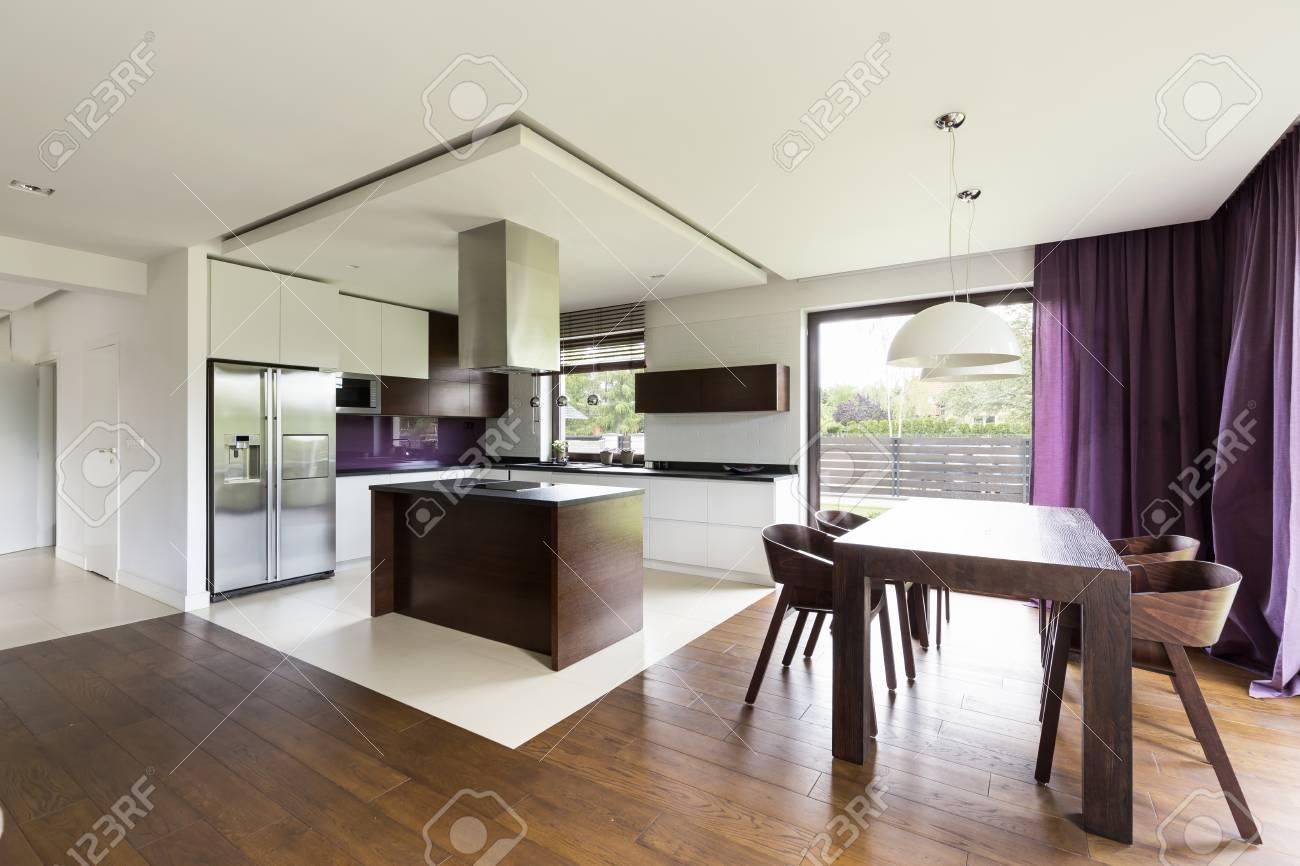 Cocina abierta de diseño moderno con isla de cocina de madera y mesa de  comedor de madera
