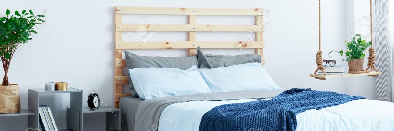 Holzbett Und Blaue Bettwäsche Im Gemütlichen, Modernen Schlafzimmer  Standard Bild   81377474