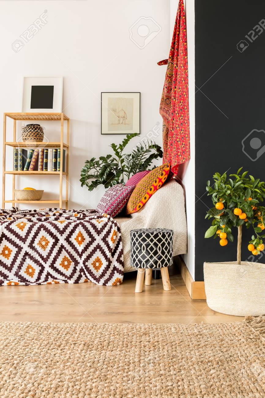 Camera da letto orientale moderna con albero arancione e libreria